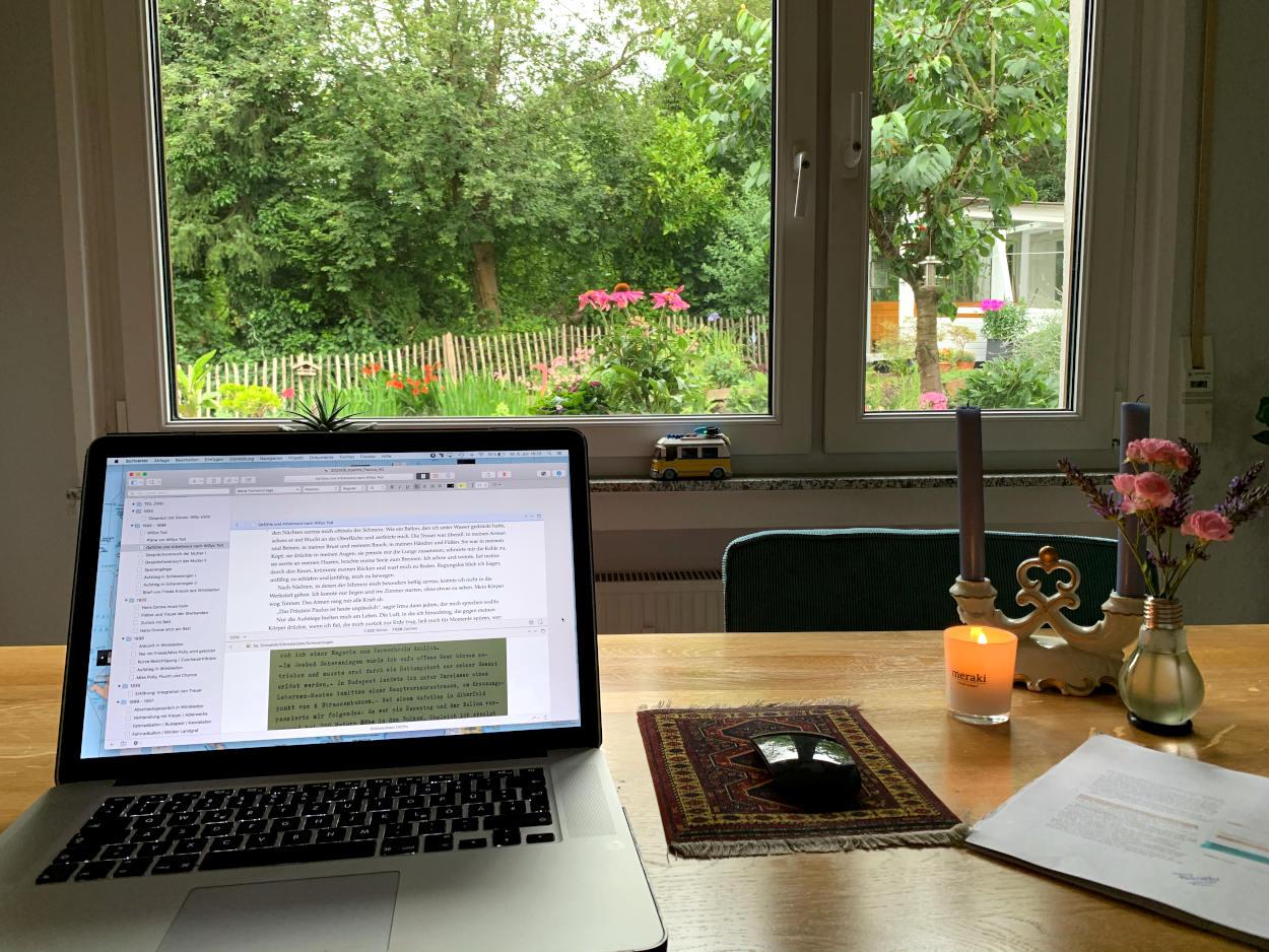 Aufgeklappter Laptop, Esstisch, Blick in den Garten, eine enzündete Duftkerze, Blumenstrauß