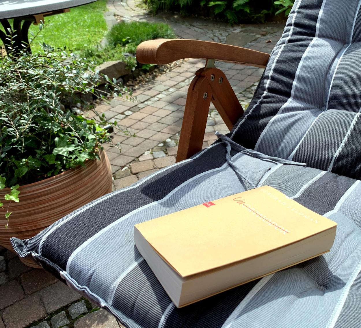"""Buch """"Unorthodox"""" auf Gartenstuhl"""