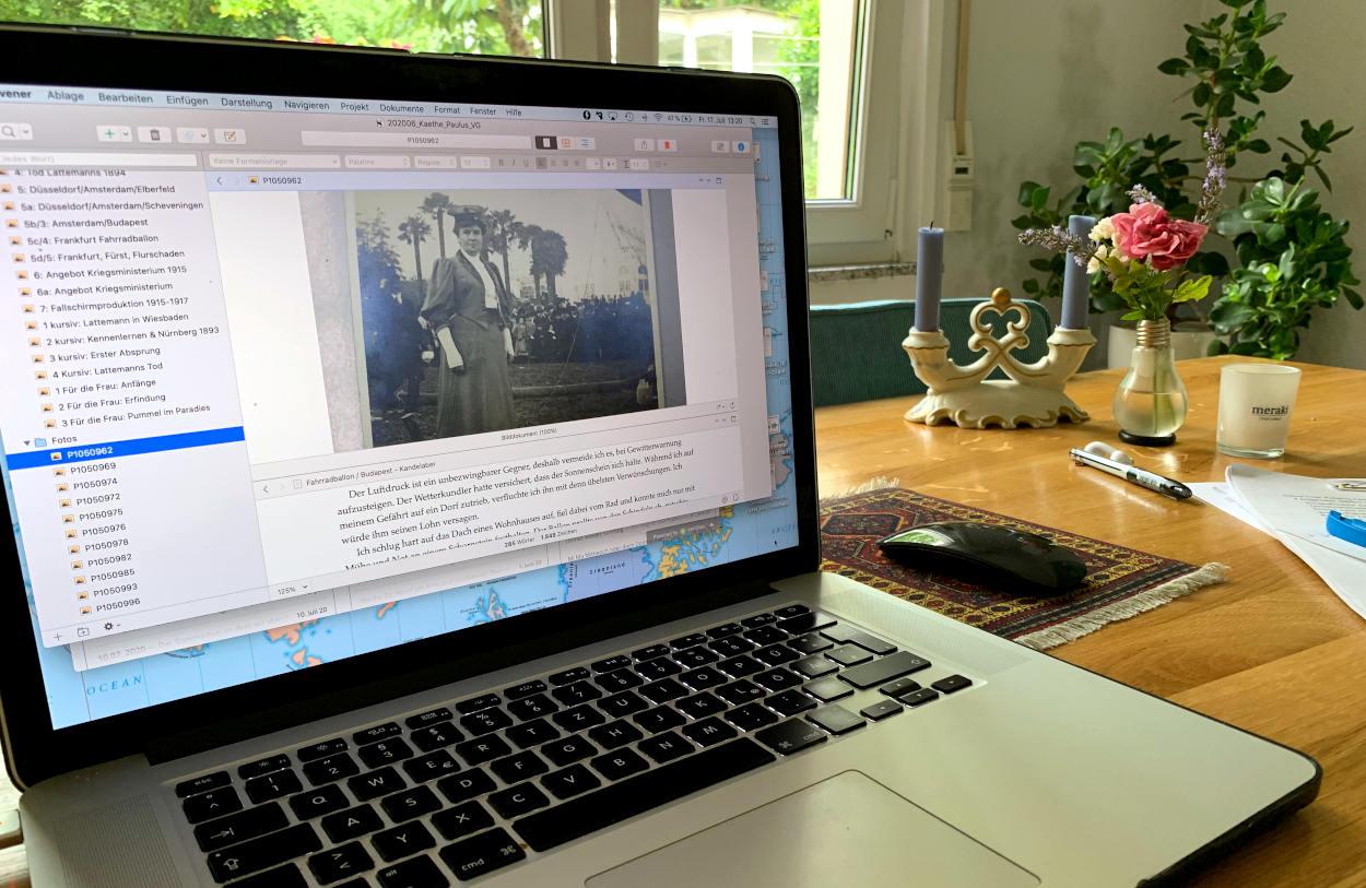 Laptop mit Portrait von Käthe, Esstisch, dahinter ein Fenster