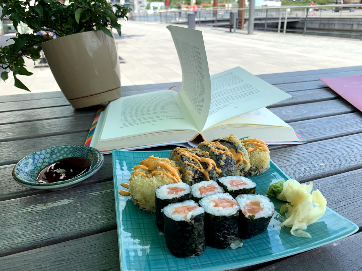 Sushi-Teller, Buch, Sojasoße, dahinter Promenade Phoenixsee