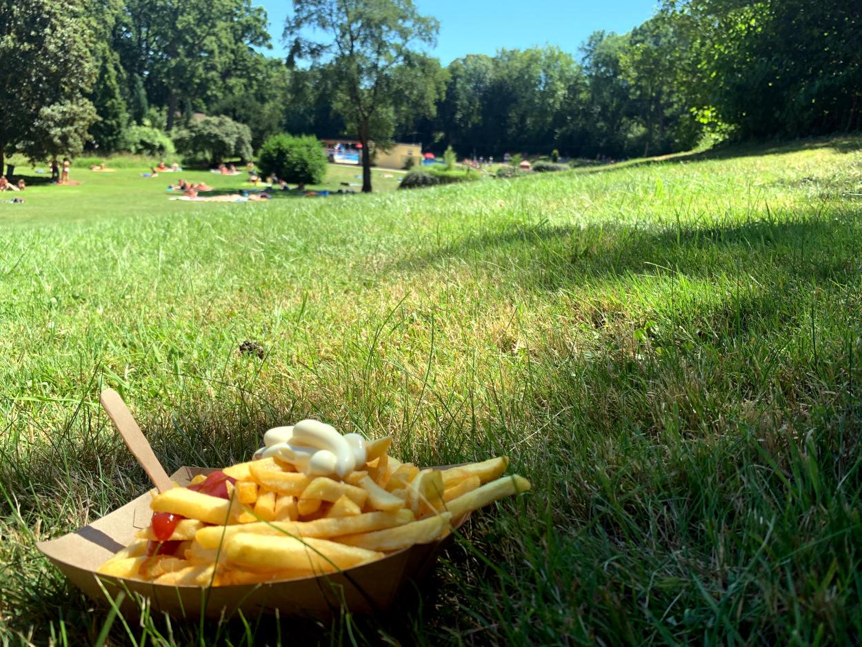 Schale Pommes im Gras, in der Ferne das Blau des Schwimmbeckens