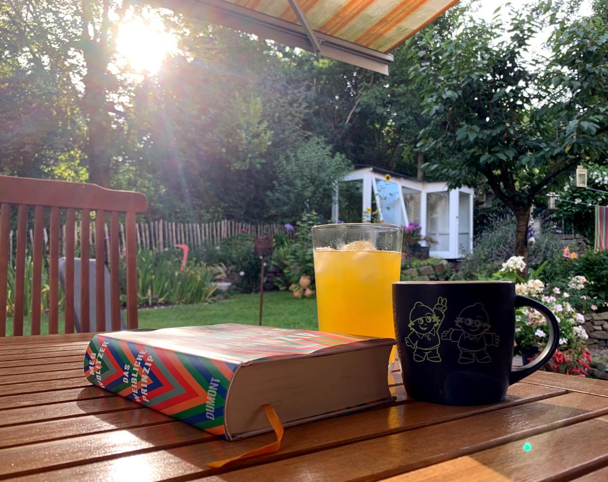 Buch mit einer Tasse Kaffee vor Gartenkulisse in der Morgensonne