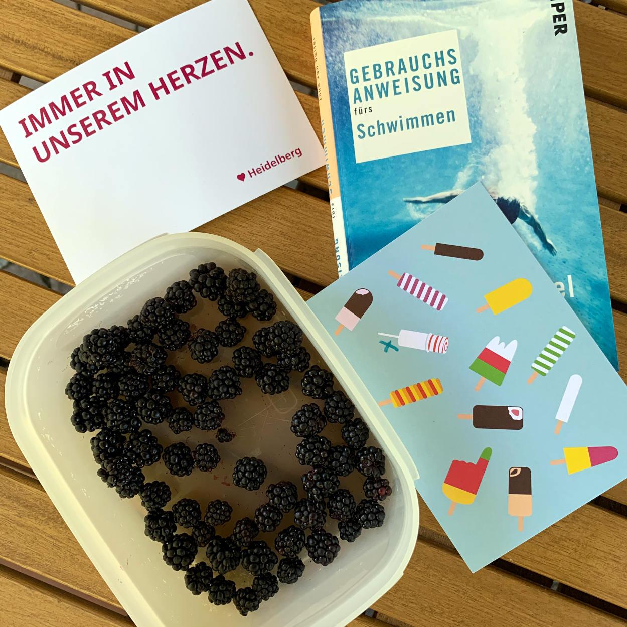"""Zwei Postkarten, eine mit Eis und eine mit der Aufschrift """"Immer in unserem Herzen - Heidelberg"""", Buch """"Gebrauchsanweisung fürs Schwimmen, eine Schale mit Brombeeren"""