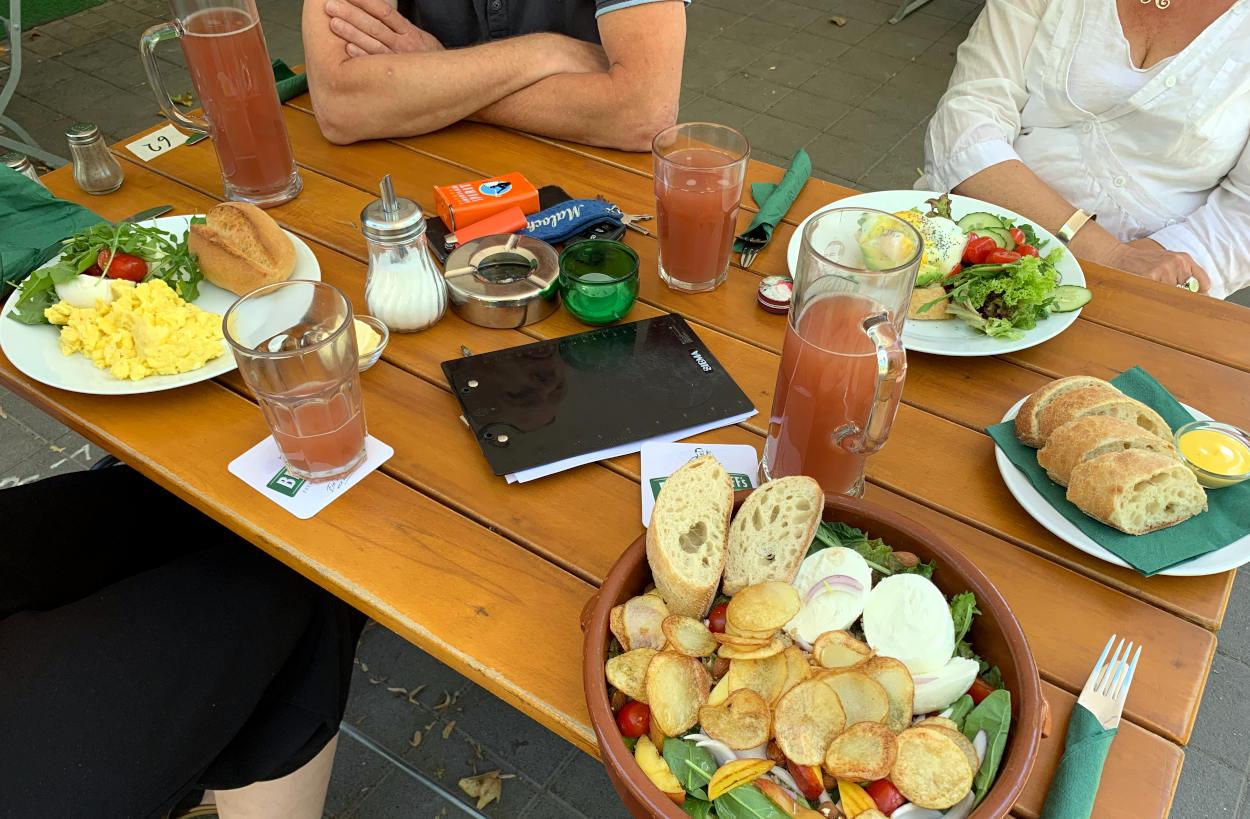 Biergartentisch von oben, vier Menschen sitzen daran. Darauf: Rhabarberschorlen, Salat, Rührei, Brot.