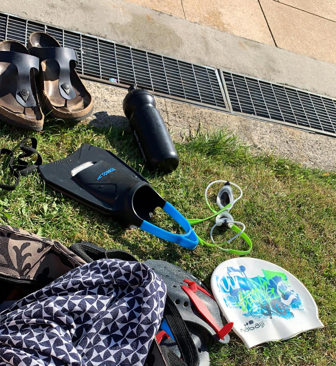 Schwimmutensilien auf der Wiese: Flossen, Brille, Paddles, Padekappe, danenebn Birkenstock und eine Tasche mit einem Kleid