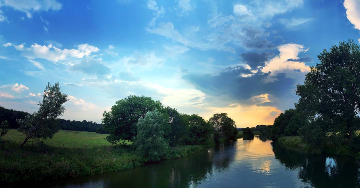 Ruhr, daneben sattgrüne Wiesen, blau-roter Himmel
