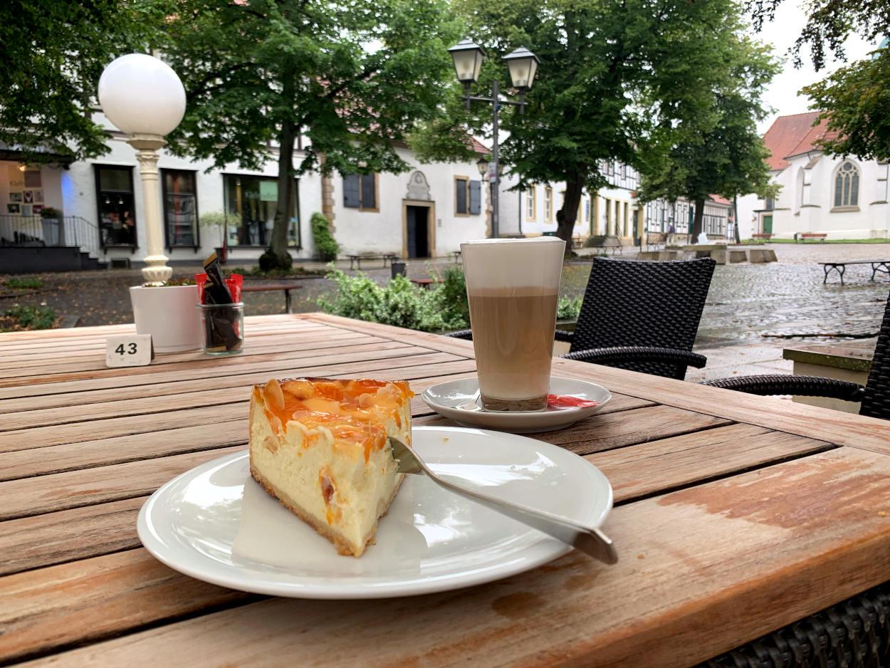 Käsekuchen, Latte Macchiato vor verregnetem westfälischen Platz mit Bäumen und Kirche