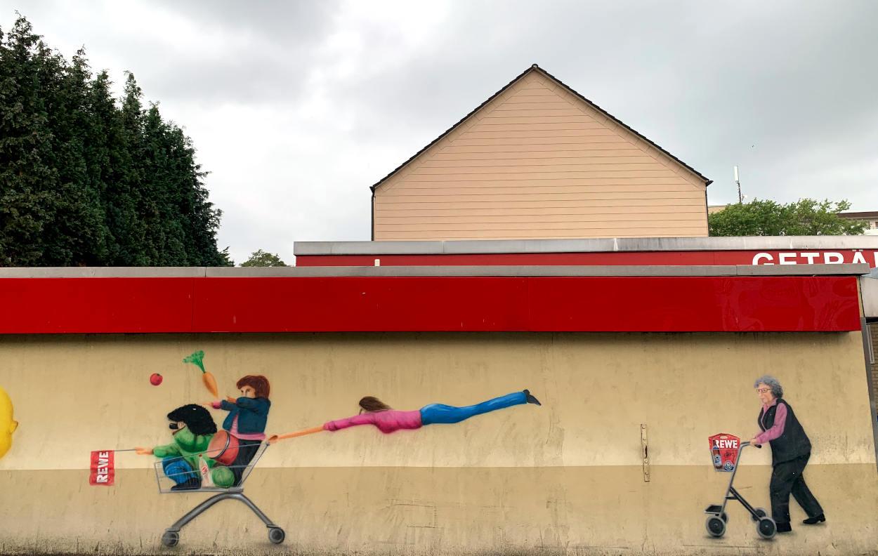 Graffiti: Kinder im EInkaufswagen, dahinter eine fliegende Frau und eine Oma mit Rollator.