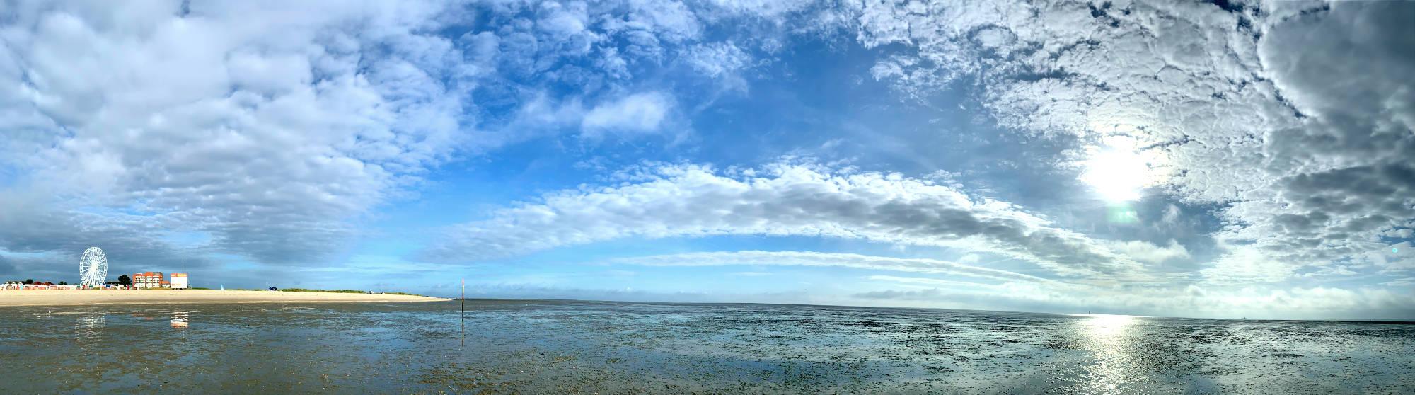 Panoramabild aus dem Watt, links der Strand mit einem Riesenrad. Die Wolken bilden einen Bogen.