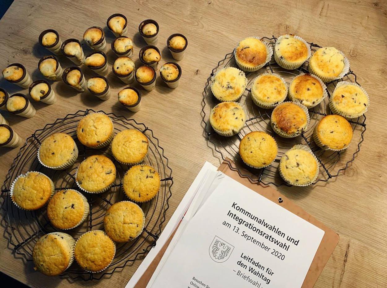 Abkühlgitter mit Muffins, kleinen Waffelbecherküchlein und daneben der Leitfaden zum Wahltag der Stadt Dortmund