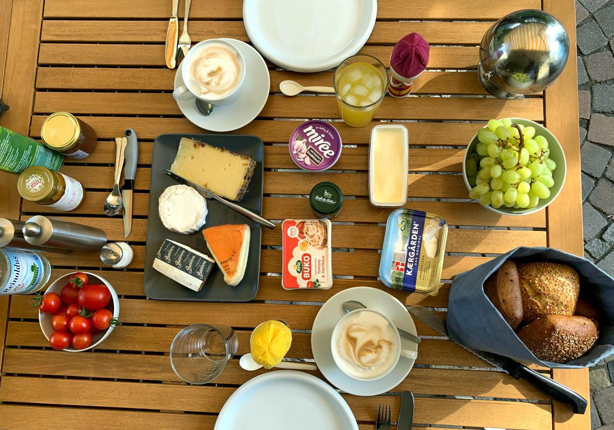 Frühstückstisch von oben mit allerlei Käse, Trauben, Tomaten und Milchkaffee