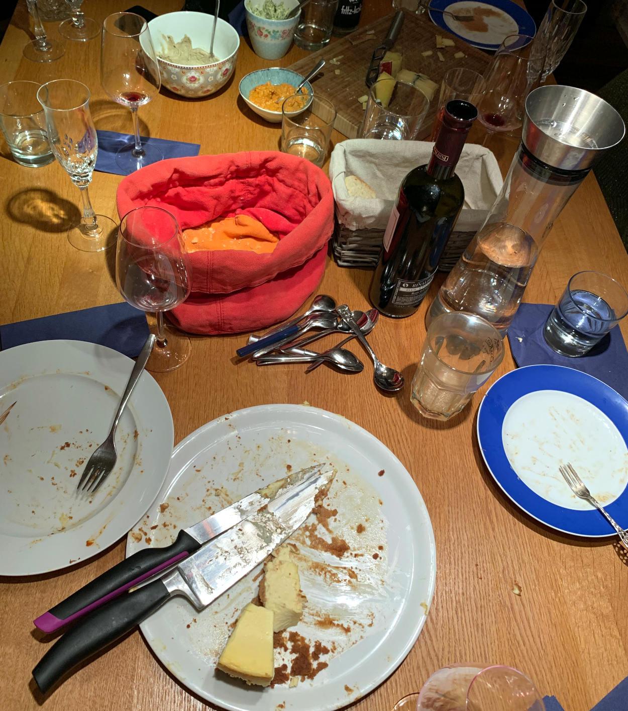 Tisch mit leeren, schmutzigen Tellern, einem leeren Brotkorb, einem Rest Käsekuchen, Gläsern und einer Weinflasche