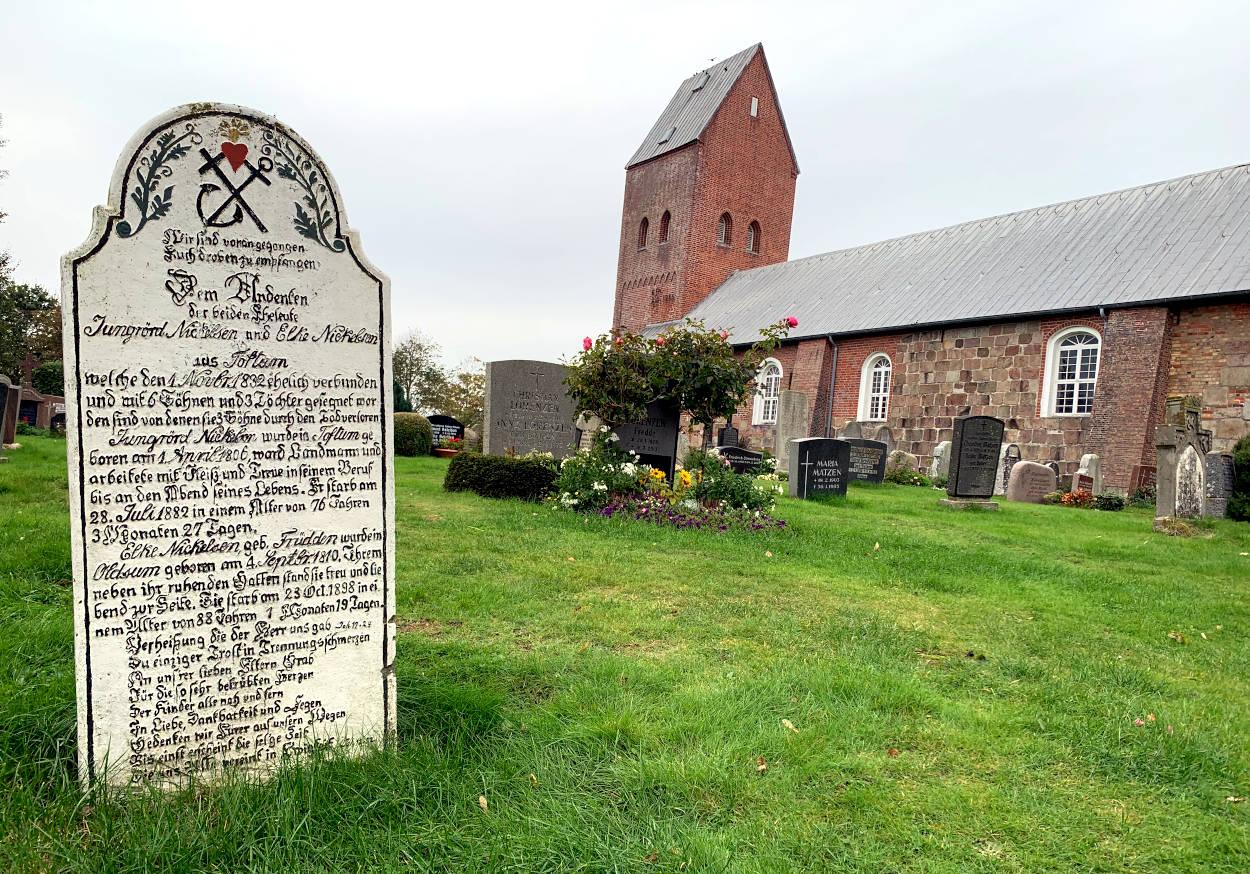 Großer Grabstein mit langer Inschrift, dahinter eine Backsteinkirche