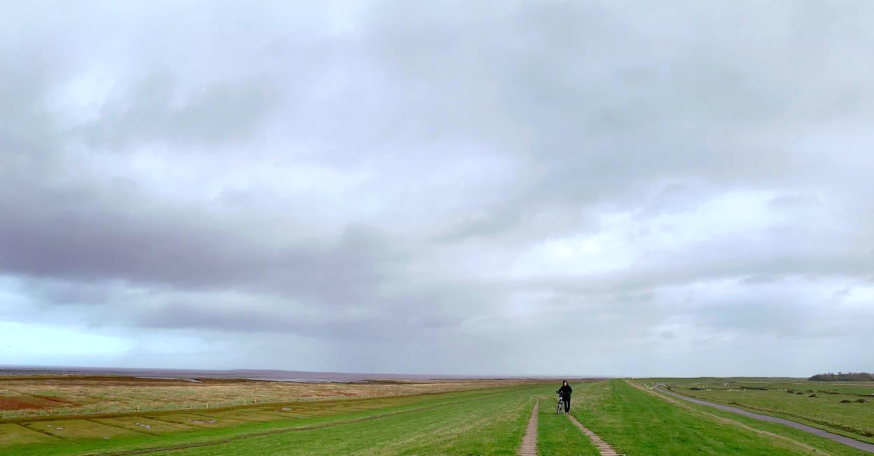 Deich, weite Landschaft, eine Frau schiebt ein Fahrrad.