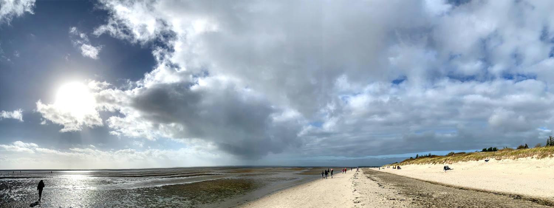 Panoaramaaufnahme vom Strand mit Sonne und Ebbe