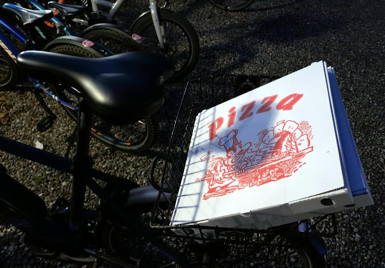 Pizza im Fahrradkorb bei Dunkelheit