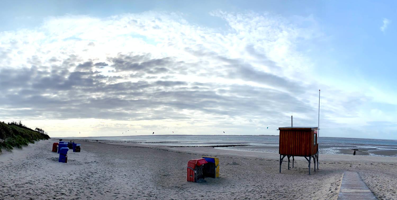 Panoramabild aufs Wasser. Am Strand ein DLRG-Haus auf Stelzen und Strandkörbe.