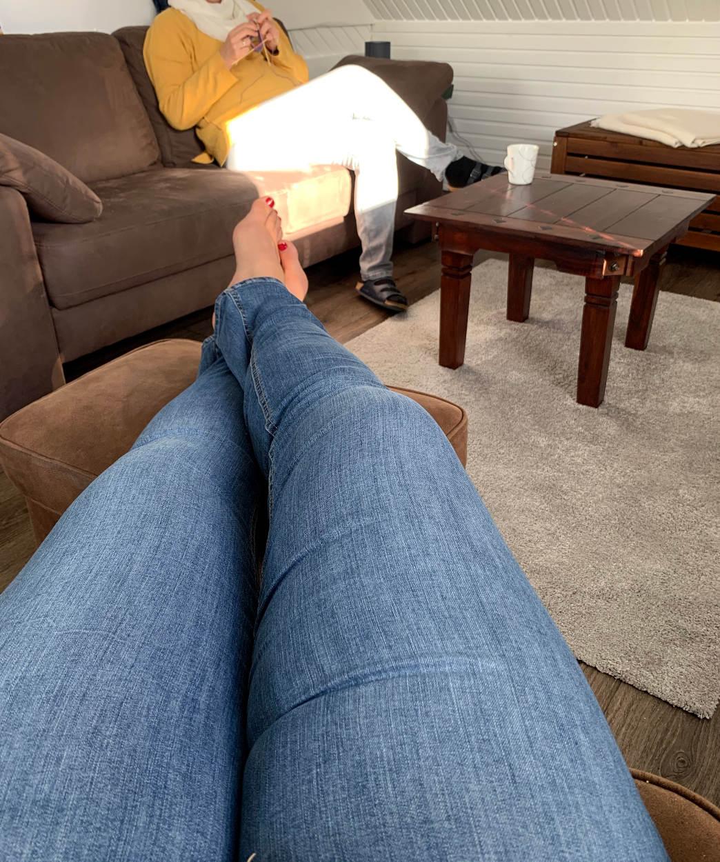 Blick über hoch gelegte Beine in Jeans zu einer strickenden Frau