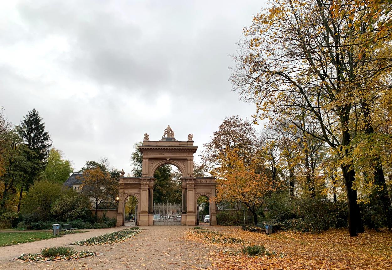 Herbstlicher Parkweg mit einem antiken, hohen Tor, gelbe Blätter