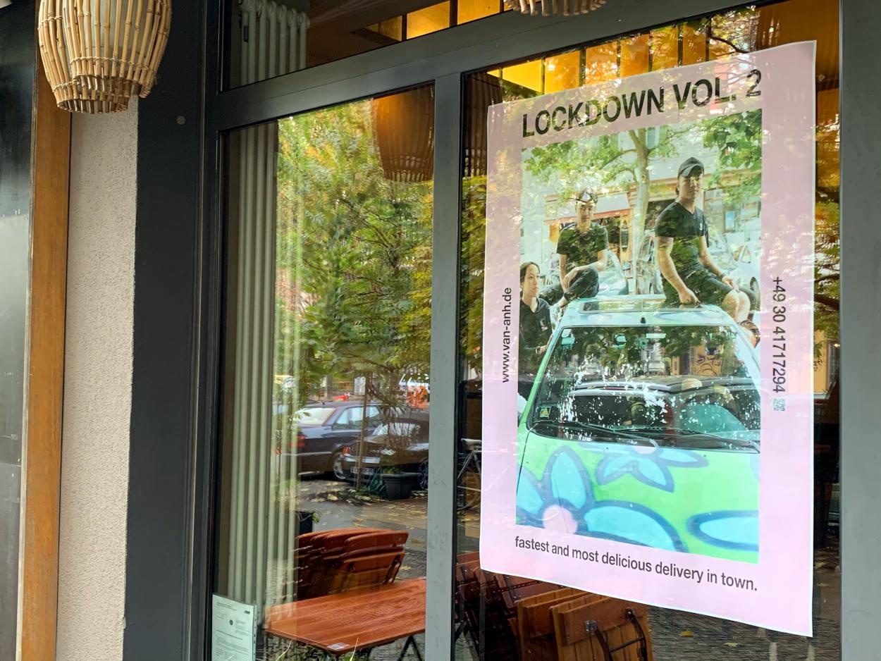 """Plakat im Fenster eines Restaurants: Drei Leute auf einem Auto. Text: """"Lockdown Vol.2. Fastest and most delicious delivery in town"""""""