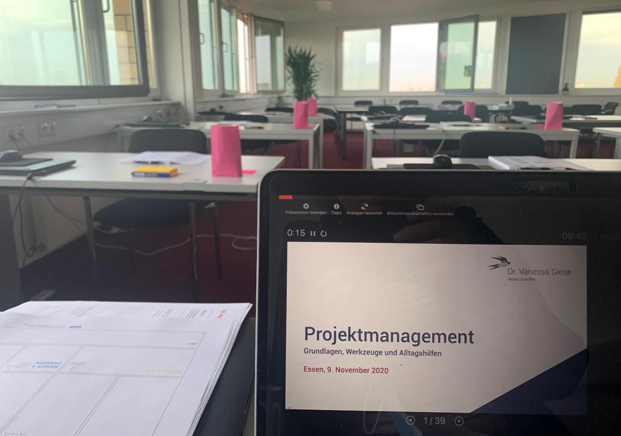 """Laptop mit Folien """"Projektmanagement - Grundlagen, Werkzeuge, Alltagshilfe"""". Dahinter ein leerer Seminarraum."""