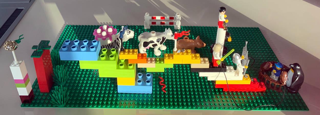 Bau aus Legosteinen: Tiere, Treppe und rechts ein Männchen mit einem Pinguin