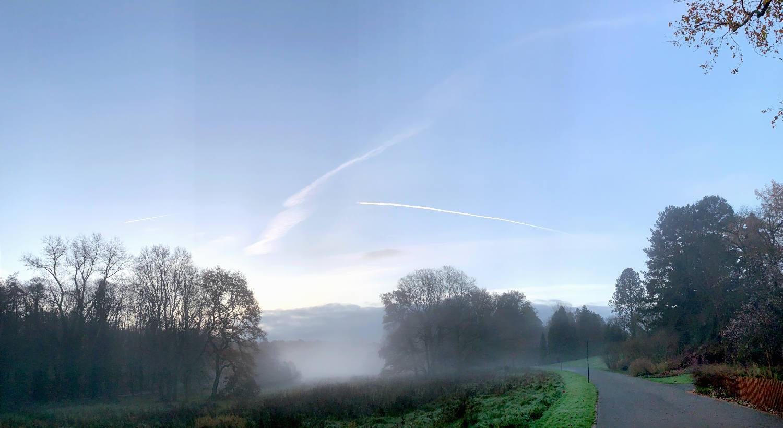 Morgendämmerung, Nebel liegt in den Feldern. Rechts ein asphaltierter Parkweg.