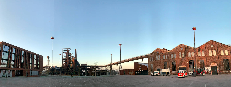 Hochofenkulisse auf 11 Uhr, daneben Industriehallen.