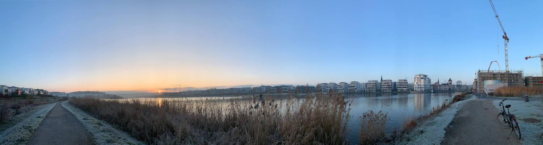 Panoramabild_ Weg geht nach links und rechts weg, der Blick geht über den See bei Sonnenaufgang. Rechts Kräne und ein abgestelltes Fahrrad.