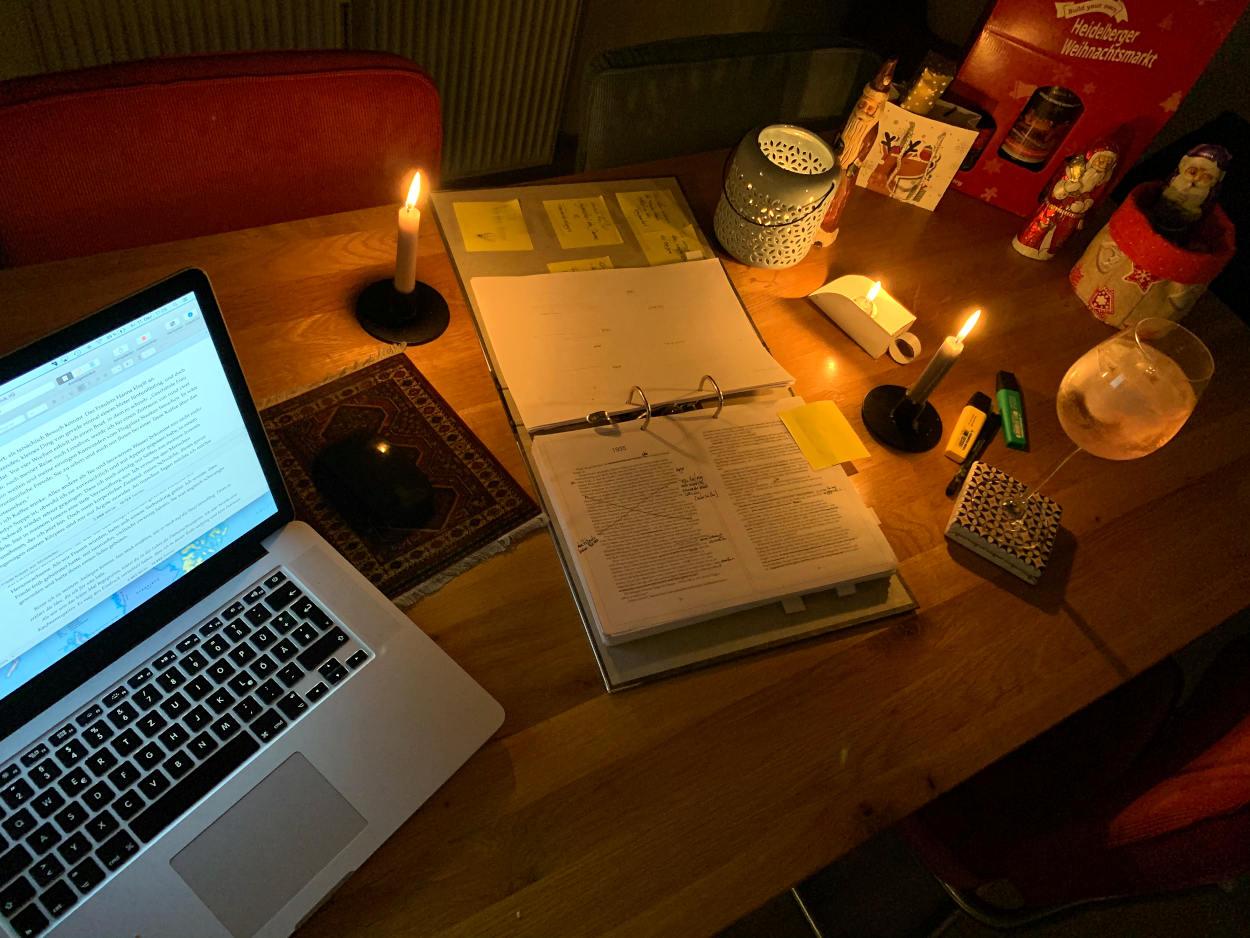 Esstisch mit Laptop und einem Ordner mit korrigiertem Text. Kerzenschein. Ein Weinglas mit Lillet.