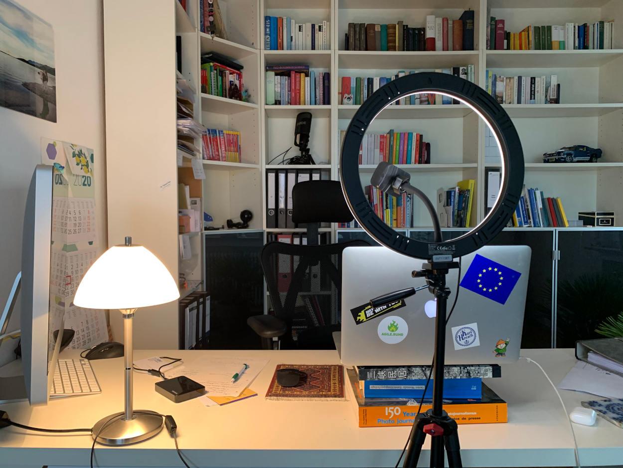 Arbeitsplatz: Im Hintergrund Bücherregal, vor Schreibtisch mit Laptop und Ringleuchte