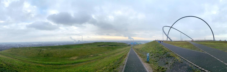 Panoramabild auf der Halde - rechts die Ringe des Observatoriums, links grüne Hügel und Wege.