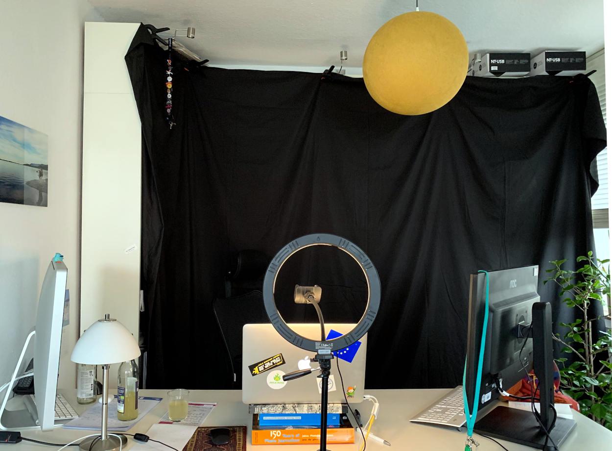 Schreibtisch mit Laptop und zwei Monitoren, dahinter Billiy-Regale, mit schwarzen Stoff verhangen.