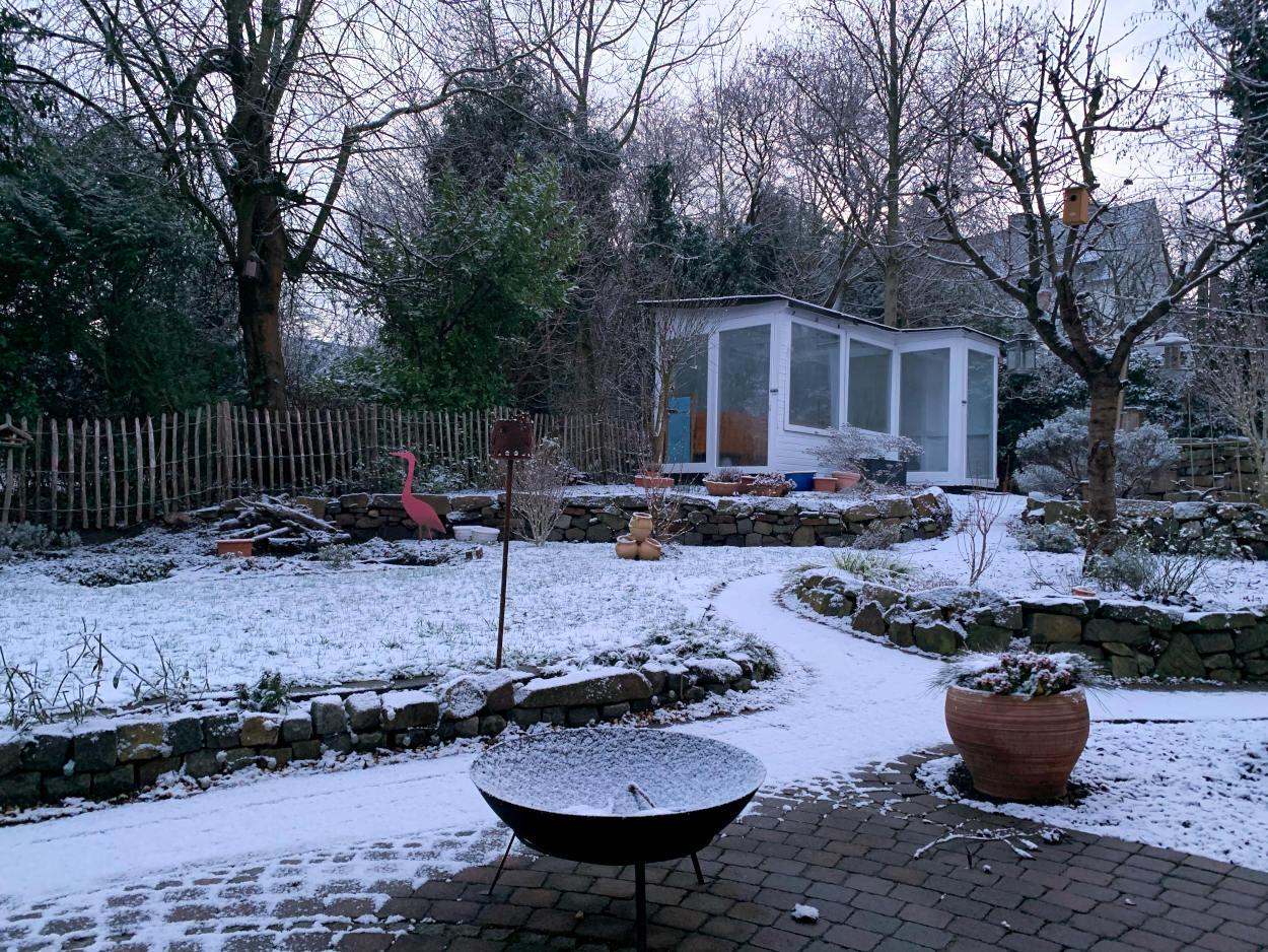 Garten, Gewächshaus und ein leichter Schneefilm. Es sieht frostig aus.