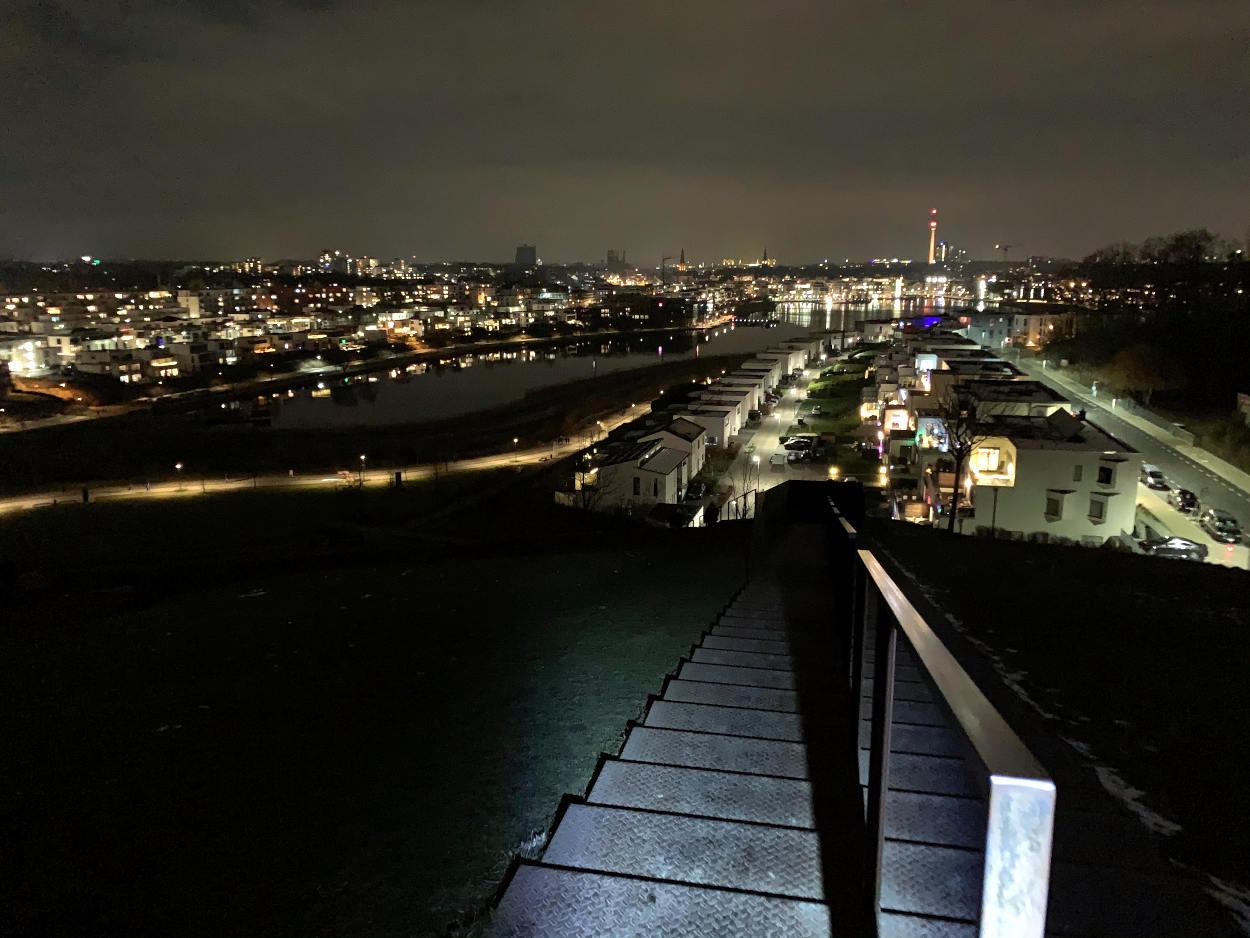 Blick vom Hügel auf den Phoenixsee, Großstadtlichter. Es ist ansonsten dunkel.
