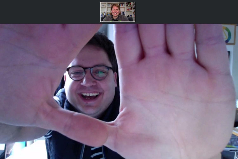 Screenshot aus der Videokonferenz. Daniel guckt durch seine Hände und verdeckt dadurch das Zimmer. Auf 12 Uhr ein kleines Bild von Vanessa.