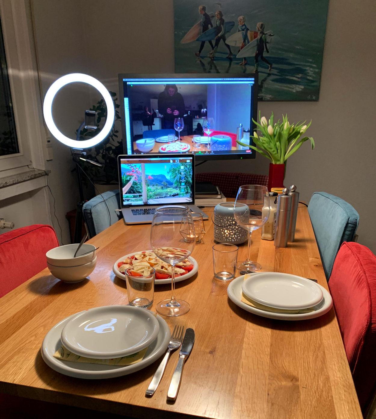 Esstisch mit zwei Gedecken, am Kopfende ein Monitor und ein Laptop.
