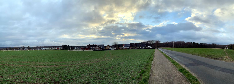 Panoramabild vom Land: Rechts etwas leere Straße, links Feld. Himmel mit Wolken.