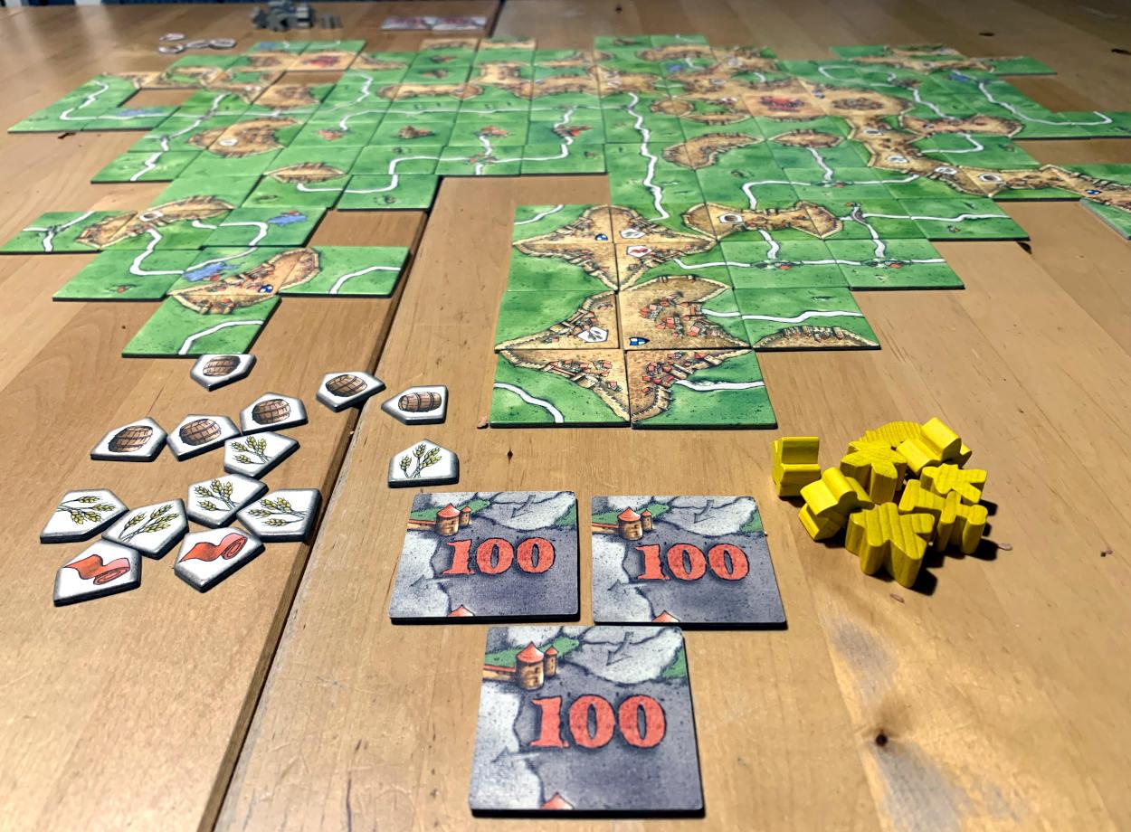 Carcassone-Spielfeld, davor jede Menge Rohstoffplättchen und 300 Punkte
