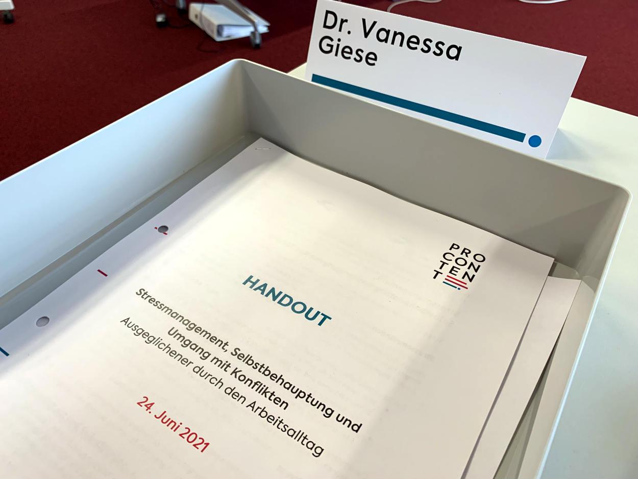 """Zettel in einer Ablage: """"Handout: Stressmanagement, Selbstbehauptung und Umgang mit Konflikten"""", dazu das aufgestellte Namensschild """"Dr. Vanessa Giese"""""""