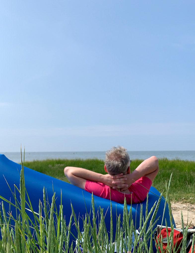 Mann in pinkem Shirt auf Luftsofa, aufs Meer schauend