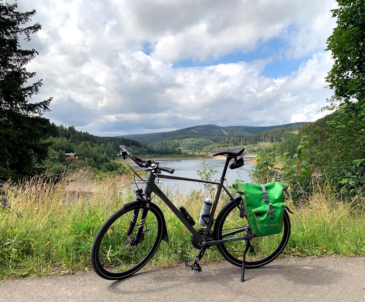 Fahrrad vor Okersee, der Sattel ist hoch eingestellt. Auf dem Gepäckträger eine Fahrradtasche.