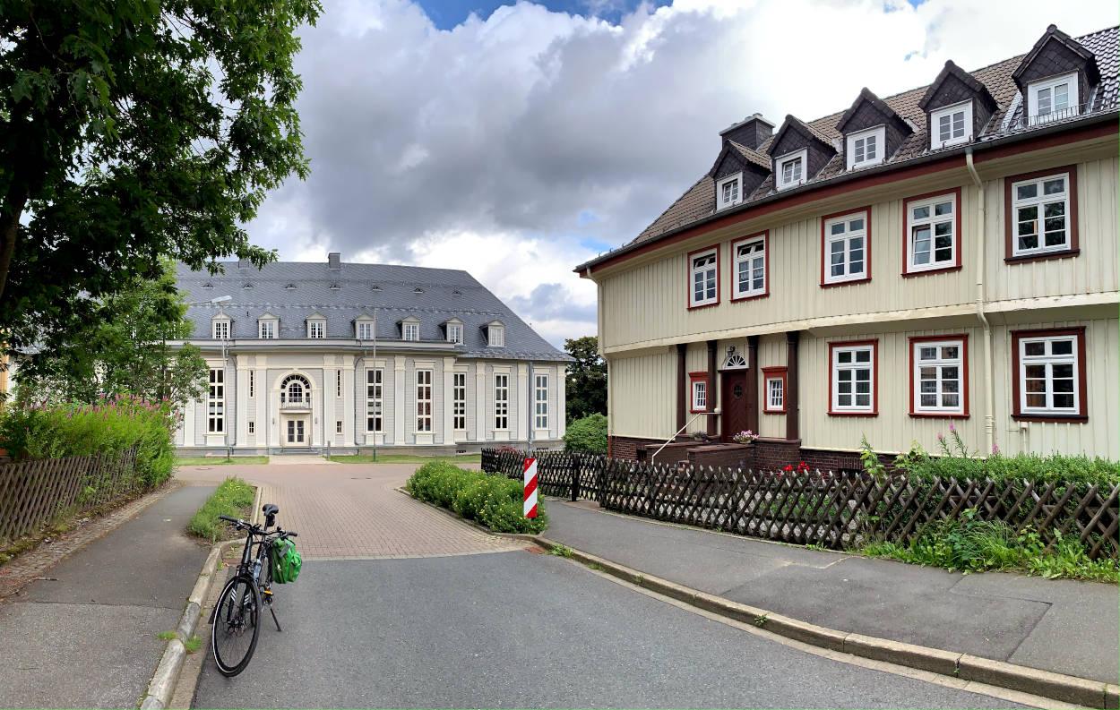 Straße, vor Kopf ein graues, ehrwürdiges Holzgebäude, rechts eine weniger prunkvolle, aber gepflegte Häuserreihe in weiß-rot