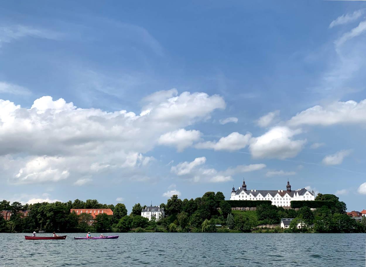 Bild vom Wasser aus mit Blick auf das Plöner Schloss. Davor zwei Boote.