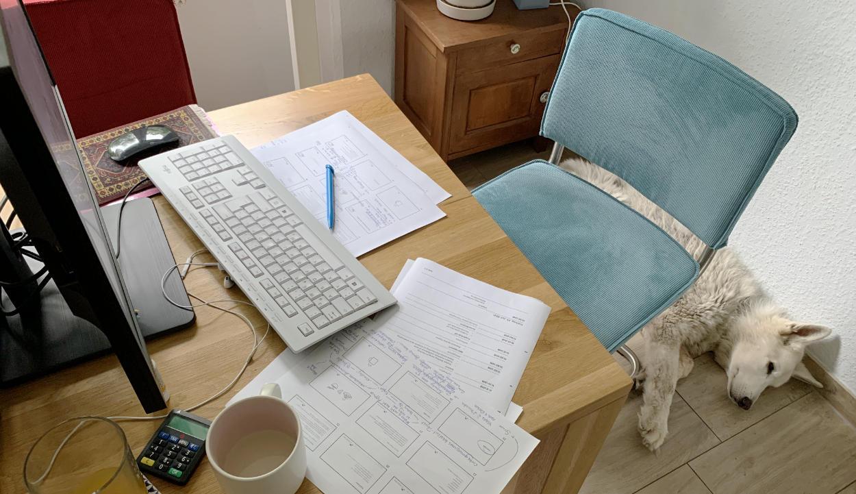 Hund hinter Esstischstuhl, auf dem Tisch Notizen, Tastatur, Monitor