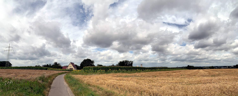 Panoramabild von einem abgeernteten Feld, in der Ferne ein Haus, Sonnenblumen. Himmel mit Wolken