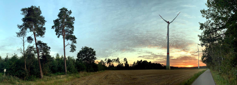 Panoramaaufnahme : Feld, ein bisschen Wald, zwei Windräder, Sonnenuntergang