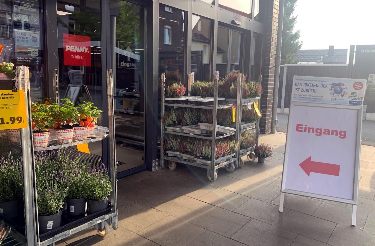 """EIngang zum Supermarkt. Davor ein Klappschild mit dem Wort """"Eingang"""" und einem Pfeil"""